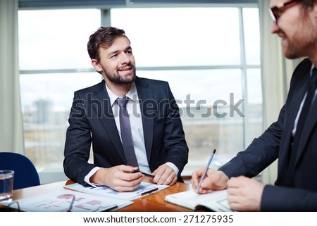 Young businessman listening to his colleague at meeting - stock photo