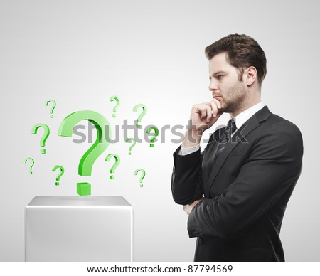 Young  businessman look at the green question marks on a white pedestal. On a gray background