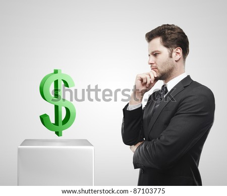 Young  businessman look at the green US dollar sign on a white pedestal. On a gray background - stock photo