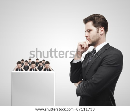 Young  businessman look at the group of businessmen on a white pedestal.Thinking men representing a social network. Conceptual image of a open minded men.On a gray background - stock photo