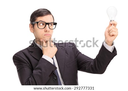 Young businessman looking at a light bulb and thinking isolated on white background - stock photo