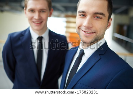 Young businessman looking at camera with his colleague on background - stock photo