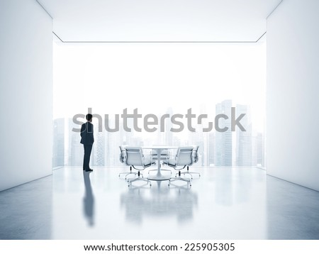 Young businessman looking at city through window - stock photo