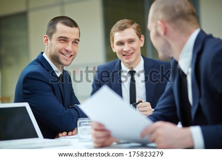 Young businessman looking at colleague during conversation - stock photo