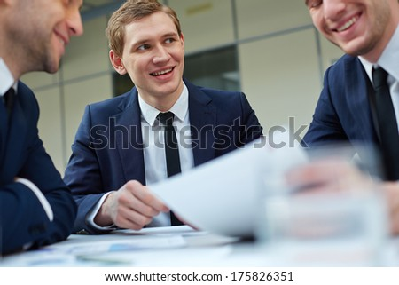 Young businessman looking at colleague during paperwork at meeting - stock photo