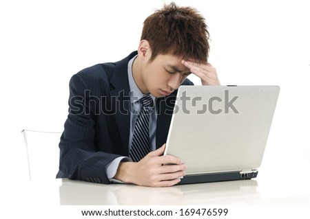 Young businessman looking at computer in desperation - stock photo