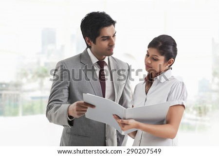 Young businessman looking at female colleague with document in hand - stock photo
