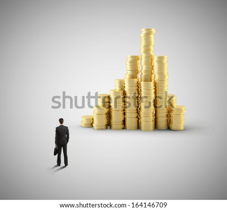 young businessman looking at gold coin city - stock photo