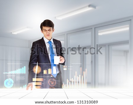 young businessman looking at graph of high-tech image - stock photo