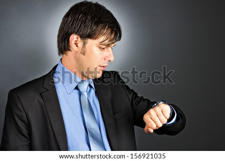 Young businessman looking at his watch against gray background - stock photo