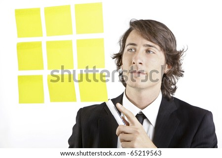young businessman looking at postit reminder notes - stock photo