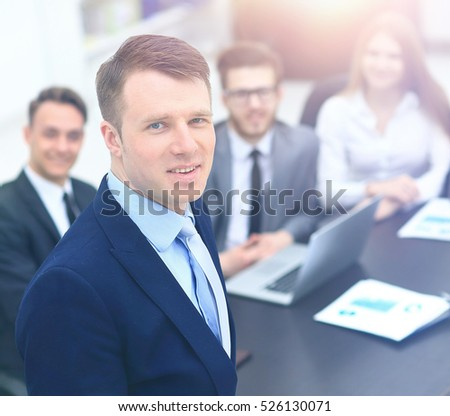 young businessman looking at the camera on the background of his team