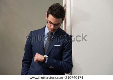 Young Businessman Looking At The Time On His Wrist Watch - stock photo