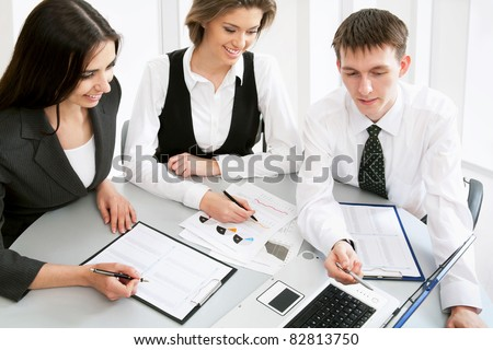 Young businessman looking at using laptop with his colleagues