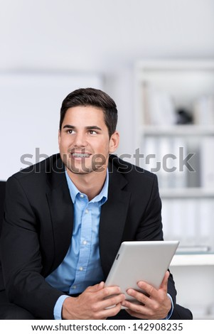 Young businessman looking away while holding digital tablet in office - stock photo