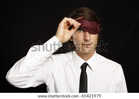 young businessman looking below sleep mask - stock photo
