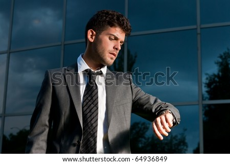 Young businessman looking clock at night on modern building background - stock photo