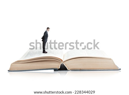 Young businessman looking into an Open book