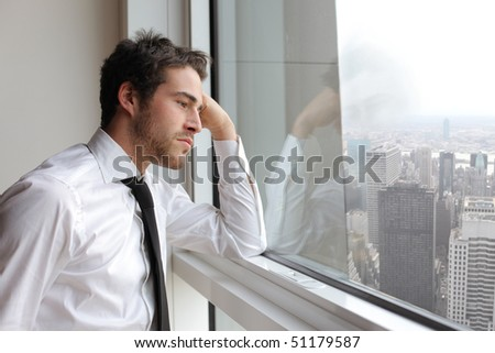 Young businessman looking out of a window - stock photo