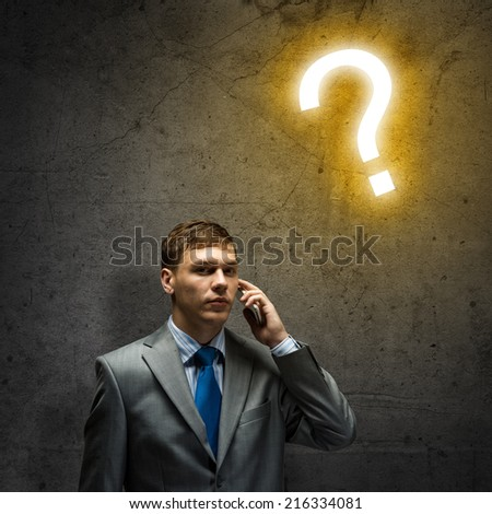 Young businessman looking thoughtfully at question mark