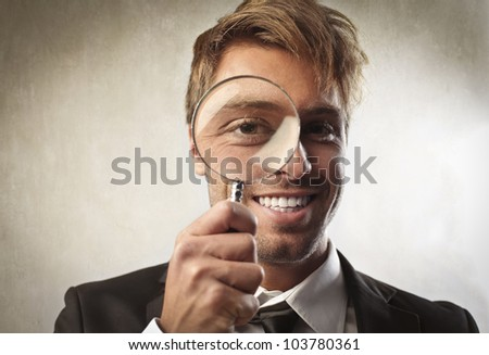 Young businessman looking through a magnifying glass