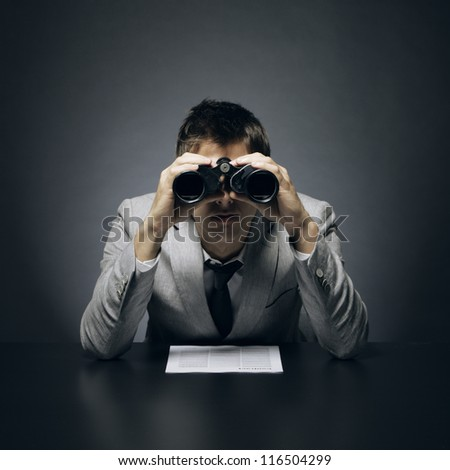 Young businessman looking through binoculars - stock photo