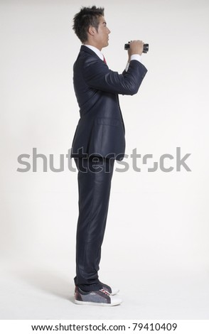 young businessman looking through binoculars. - stock photo