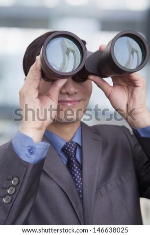 Young businessman looking through binoculars, Beijing - stock photo