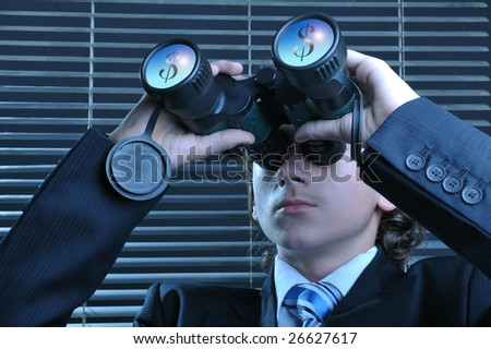 Young businessman looking through binoculars, dollar sign reflected on lens - stock photo