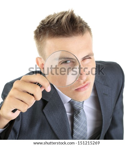 Young businessman looking through magnifying glass isolated on white - stock photo