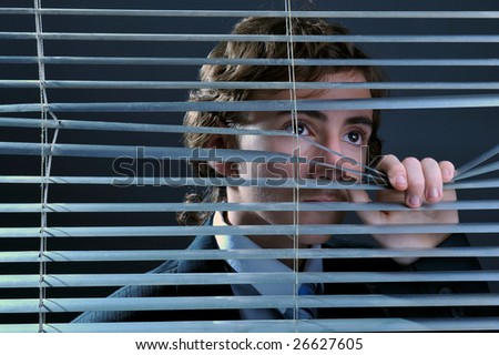 Young businessman looking through window blinds - stock photo