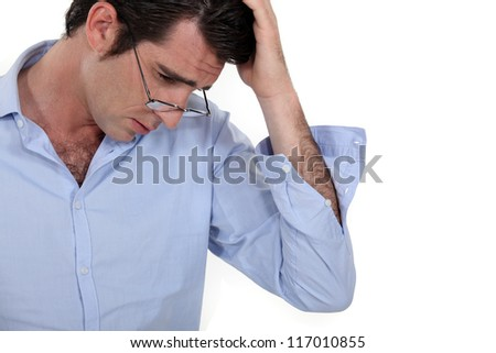 young businessman looking tired with glasses lowered and hand to his head - stock photo
