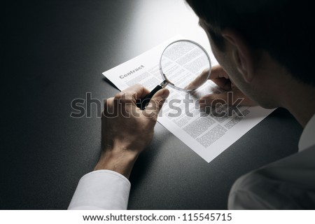 Young businessman looking to a contract through a magnifying glass