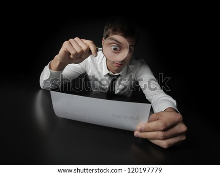 Young businessman looking to a contract through a magnifying glass - stock photo
