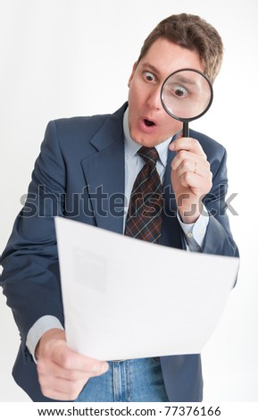 Young businessman looking to a document through a magnifying glass - stock photo