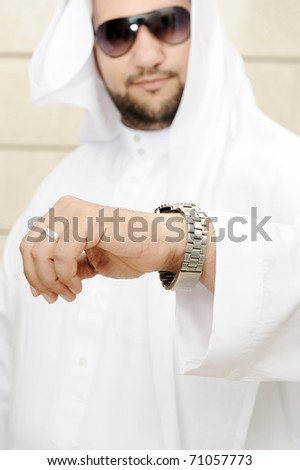 young businessman looking to his hand watch