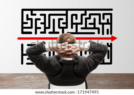 young businessman looking to maze on white wall - stock photo