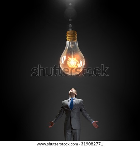 Young businessman looking up at glass glowing light bulb - stock photo