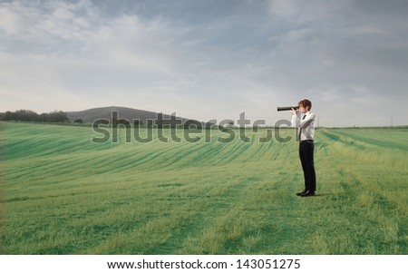 young businessman looking with spyglass in the countryside