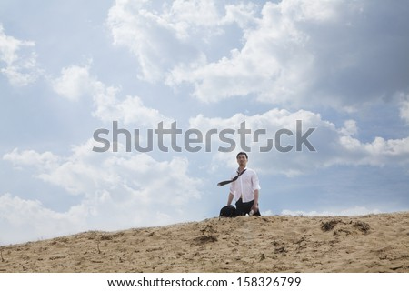 Young businessman lost and walking through the desert - stock photo