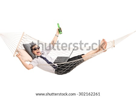 Young businessman lying in a hammock with a beer in his hand and working on a laptop isolated on white background - stock photo