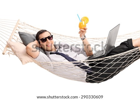 Young businessman lying in a hammock with a laptop in his lap and drinking an orange cocktail isolated on white background - stock photo