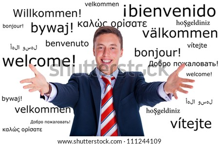 Young businessman makes a welcome gesture on a multilingual background