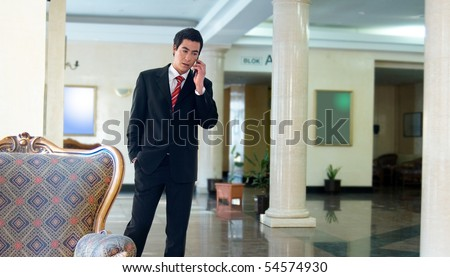 Young businessman making a mobile call in hotel lobby