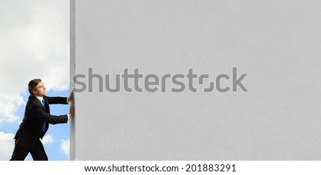 Young businessman making effort to move brick wall - stock photo