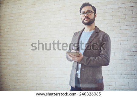 Young businessman making notes in notepad - stock photo