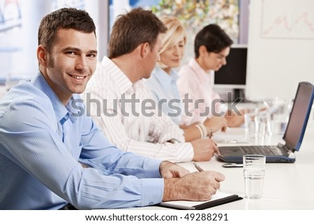 Young businessman making notes on business presentation at office, looking at camera, smiling.