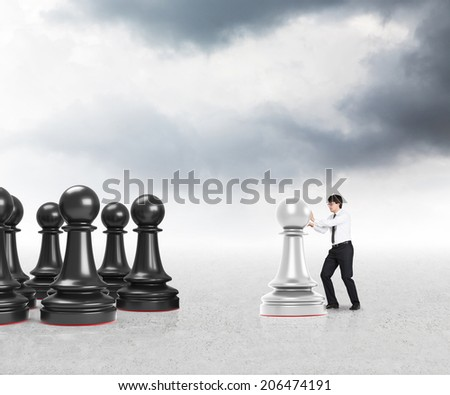 Young businessman moving a pawn on the grey desk under the silver sky. - stock photo