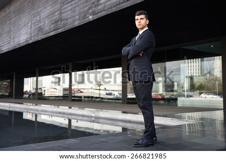Young businessman near a modern office building wearing black suit and tie. Man with blue eyes - stock photo