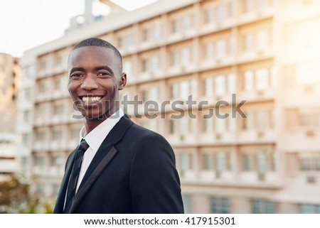 Young businessman of African descent smiling broadly outdoors - stock photo